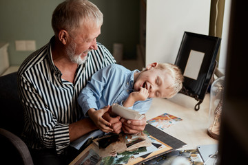 senior man and little boy holding and looking at family photo album in living room