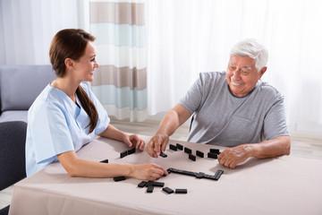 Caretaker Looking At Elder Man Playing Dominoes