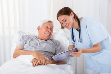 Nurse With Clipboard Visiting Senior Patient