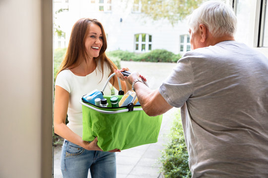 Man Offering Help To His Daughter Carrying Groceries