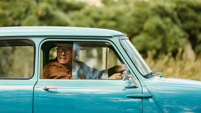 Old man driving a classic car