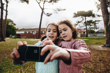 Identical twin girls taking selfie with old camera at park