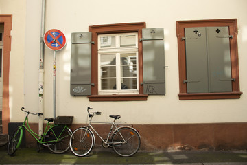 German people stopping and lock bicycle at front of classic and retro house