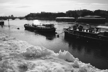 Paris under snow. View of Seine river with houseboats and flooded quay. Black and white photo.