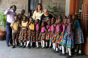 U.S. first lady Melania Trump and Kenya's first lady Margaret Kenyatta pose for a photograph with children as they arrive to watch a play at the Kenya National Theatre in Nairobi