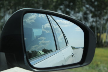 Reflection of the road, sky and clouds in the car rearview mirror