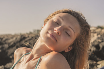 Portrait of a young pensive woman sunbathing at sunset