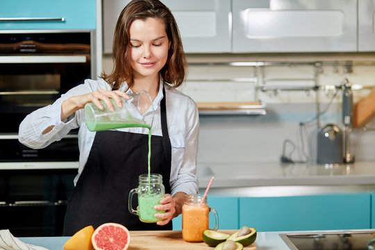 pretty woman pouring a green detox juice from blender to a glass, at home wearing casual clothes. close up photo