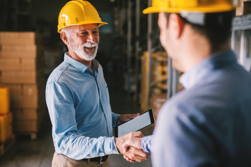 Two satisfied business man standing in warehouse with helmets on their head. Shaking hands and closing good job cooperation.