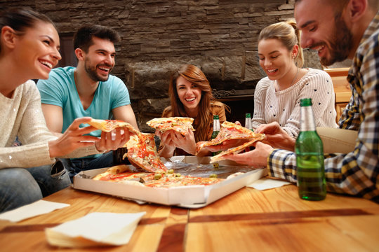 Group of young people eating's big pizza together