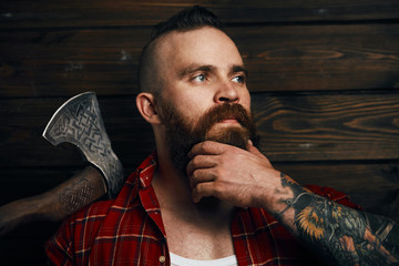 bearded mohawk male holding axe and posing in studio