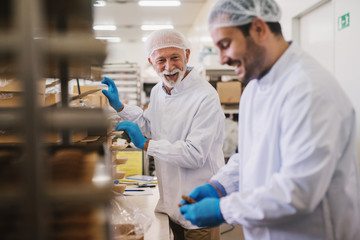 Picture of two male food factory employees in sterile clothes packing fresh made cookies and having fun.