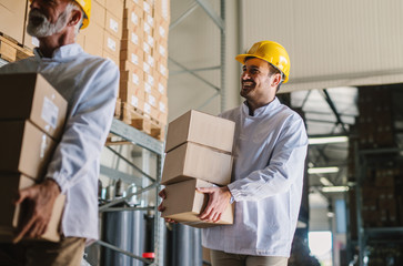 Picture of two male warehouse workers with helmets on their heads carrying boxes in their hands. Smiling and walking.