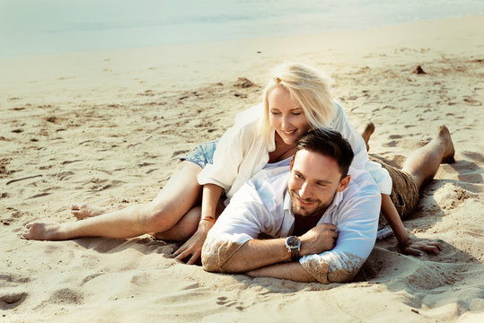 romantic couple in love enjoying vacation on the summer beach laying in sand happy smiling