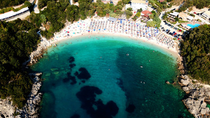 Aerial drone bird's eye view of popular beach of Sarakiniko with beautiful emerald sandy beach full of sunbeds at summer time, Epirus, Ionian, Greece