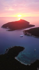 Aerial drone bird's eye view photo of iconic turquoise bay of Sivota forming a blue lagoon with beautiful colours and clouds at sunset, Ionian sea, Epirus, Greece