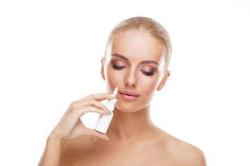 Young girl using nosal spray aerosol and drops isolated on white. Runny nose, allergy, cold and flu illness, sinusitis and healthcare medicine concept.
