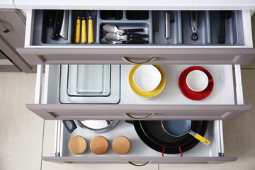 Set of clean kitchenware and utensils in drawers