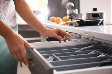Fototapeta Woman putting whisk into kitchen drawer obraz