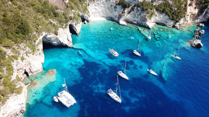 Aerial drone bird's eye view photo of sail boats docked in tropical caribbean paradise bay with white rock caves and turquoise clear sea