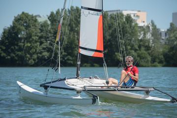 man happy on his sailboat