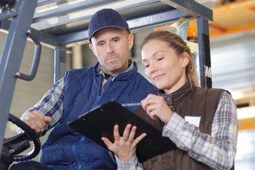 Lady showing information on clipoard to forklift driver