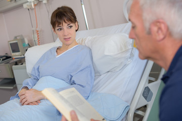 young female patient lying bed with dad