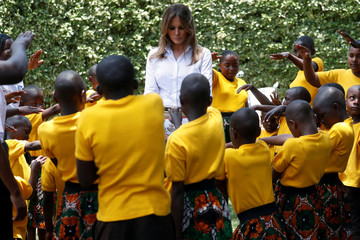 Children hold up their hands and pray for U.S. first lady Melania Trump at The Nest Children's Home in Nairobi