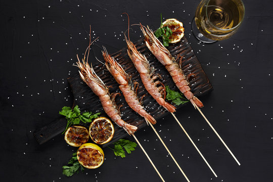 Grilled shrimp skewers. Seafood, shellfish. Shrimps Prawns skewers with herbs, garlic and lemon on black stone background, copy space.