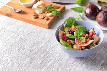 Bowl with delicious fig salad on light table