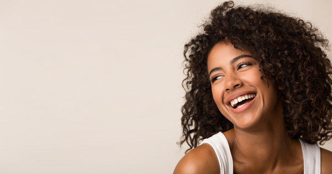 Laughing african-american woman looking away on light background