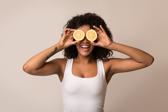 African-american woman with lemon halves near eyes