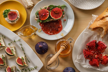 Tasty sandwiches with ripe fig and honey on wooden table
