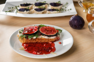 Tasty sandwich with ripe fig and jam on plate