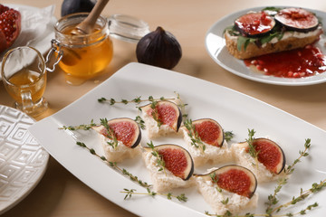 Tasty canapes with ripe fig and cream cheese on plate