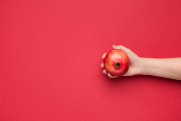 Female hand holding pomegranate on red background