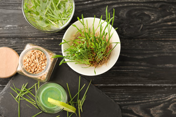 Shot of healthy juice with sprouted wheat grass and seeds on wooden table