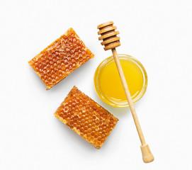 Jar full of fresh honey and honeycombs isolated on white