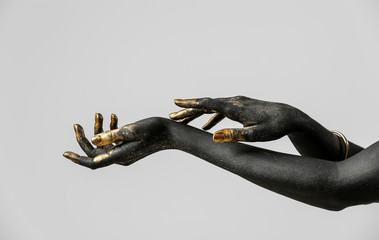 Hands of woman with black and golden paint on her body against light background