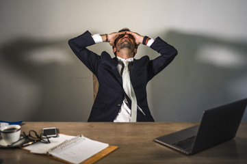 stressed businessman feeling depressed and overwhelmed working at office computer desk tired and exhausted  defeated by business financial crisis