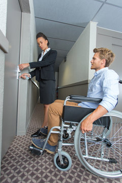 Worker opening hotel room for man in wheelchair
