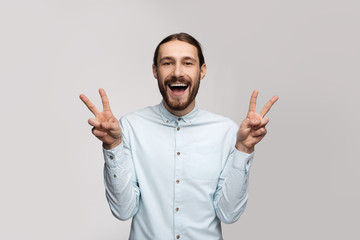 Happy cheerful office employee man in stylish glasses, casual shirt, white background, shows a funny gesture, everything cool, he likes the weekend. Website image and advertising photo isolate.