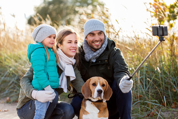 family, pets and people concept - happy mother, father and little daughter with beagle dog taking picture by smartphone on selfie  stick outdoors in autumn
