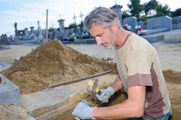 worker building a grave