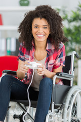 happy woman in wheel chair with joystick playing video games