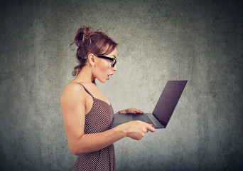young woman looking at laptop computer screen in misunderstanding and astonishment