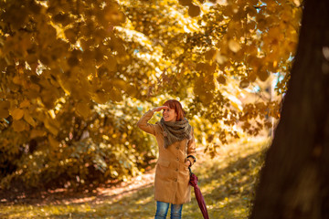 girl with red umbrella walking on autumn city park. .
