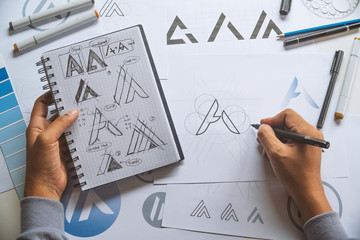 Graphic designer development process drawing sketch design creative Ideas draft Logo product trademark label brand artwork. Graphic designer studio Concept. Wall mural