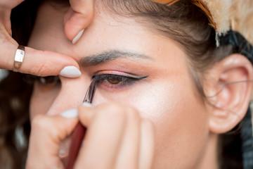 Makeup. Make-up Applying closeup. Eyeliner. Cosmetic Eyeshadows. Eyeline brush for Make up. Beauty Girl with Perfect Skin. Eyelashes. Blue eyes. Makeover