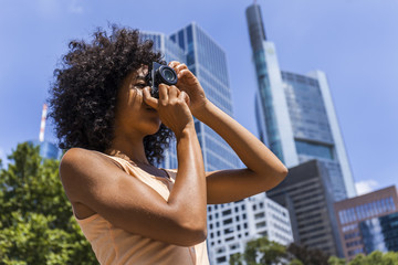 Germany, Frankfurt, young woman with curly hair taking photos in the city